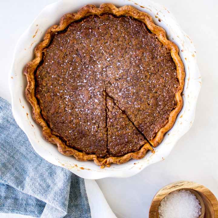 Salted maple pie is perfectly chewy, filled with sweet rich maple syrup flavor, and topped with sea salt for that irresistible salty and sweet combination. | Pass the Cookies | www.passthecookies.com